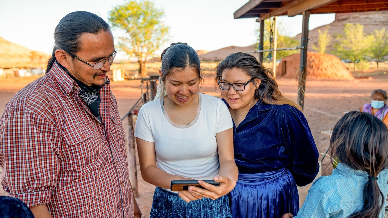 Several members of a Native tribe using a smartphone to view text notifications that provide updates on services and events